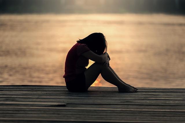 נערה בגיל ההתבגרות יושבת על המזח ליד המים