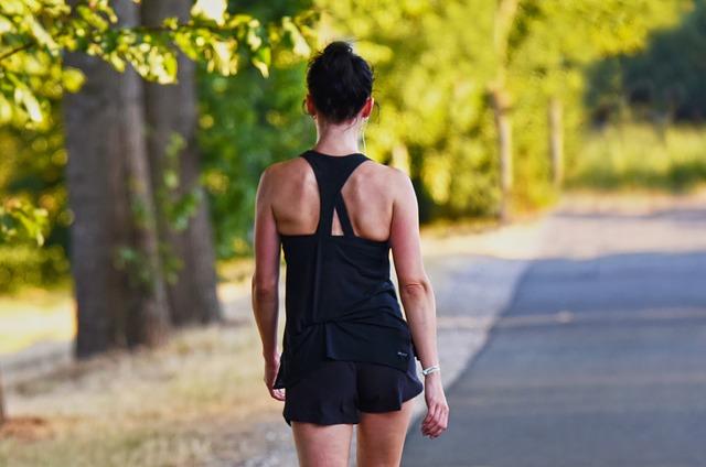 בחורה מבצעת הליכה על כביש שמצדדיו עצים