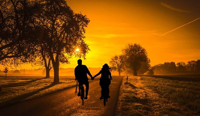 זוג רוכב על אופניים בחיק הטבע לאור השקיעה
