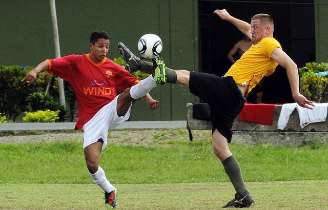 שני שחקנים נאבקים על הכדור במשחק כדורגל