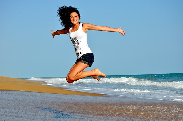 בחורה קופצת בחוף הים ונראית מאושרת