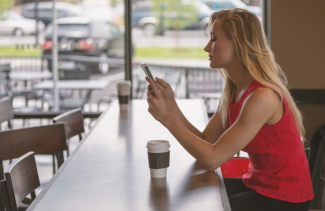 בחורה יושבת וגולשת בטלפון נייד